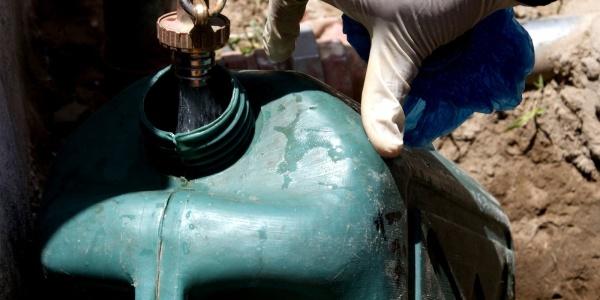 una mano con guanto in lattice apre rubinetto sopra tanica in plastica