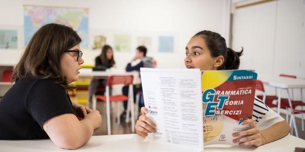 due ragazze sedute al banco di scuola una di loro con un libro di esercizi in mano parlano tra loro