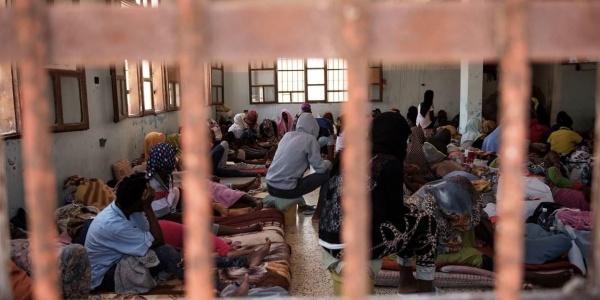 Migranti in stanza sovraffollata dietro le sbarre in centro di detenzione in Libia