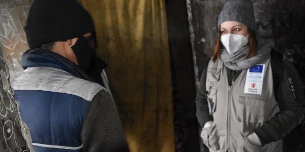 Operatrice save the children con cappello di lana grigio in testa ha di fronte a sé un minore migrante di spalle