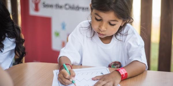 bambina seduta a un tavolo mentre fa i compiti