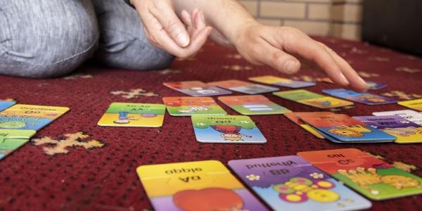 primo piano di card colorate appoggiate a terra e mani di un adulto che le tocca