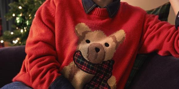 Elodie con maglione natalizio, seduta sul divano che festeggia il Christmas Jumper Day