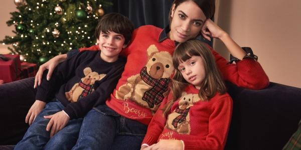 la cantante Elodie seduta su un divano insieme a una bambina e un bambino. Tutti e 3 indossano un maglione natalizio e alle loro spalle cè un albero di Natale
