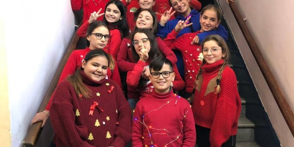 bambini sulle scale che indossano maglioni rossi