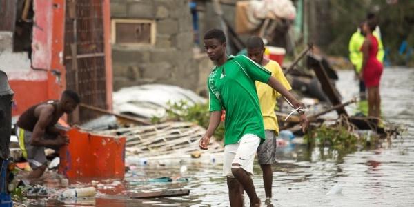 Ragazzo a piedi scalzi cammina in acqua a causa delle inondazioni.