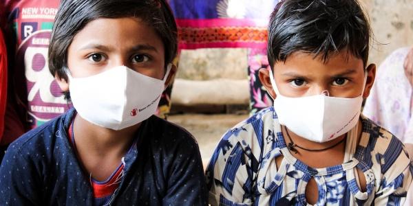 Due bambini indiani seduti vicini indossano mascherina bianca save the children. Uno ha una camicia a righe, l altro una felpa blu