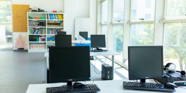 Grande sala di un Punto Luce con computer sui tavoli per le attività educative