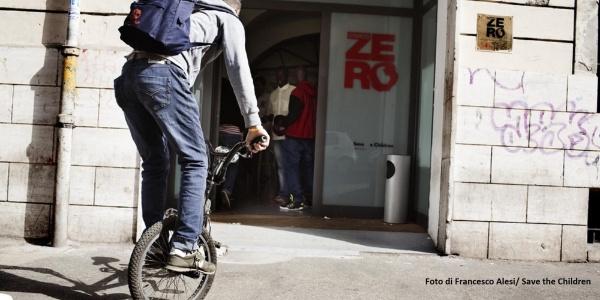 Ragazzo di spalle su monociclo davanti a entrata del centro civicozero roma