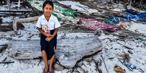 bambina asiatica seduta su un tronco di un albero in mezzo alle macerie create da un inondazione