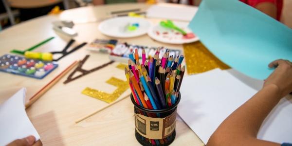 tavolo rotondo con attorno 4 bambini non riconoscibili poiché inquadrati dalle spalle in giù. Sul tavolo materiale da disegno e in primo piano un porta pastelli pieno di pastelli colorati.