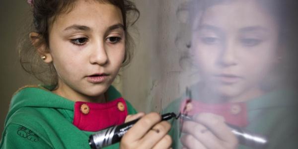 bambina scrive su una lavagna magnetica con un pennarello nero