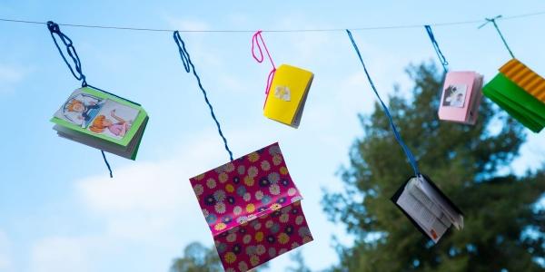 Libri e quaderni colorati appesi a un filo che si stagliano su cielo azzurro