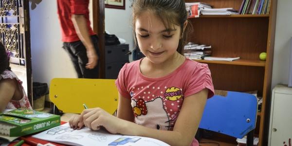 Bambina con maglietta rosa di hello kitty è seduta a un tavolino e guarda un libro mentre lo sfoglia.