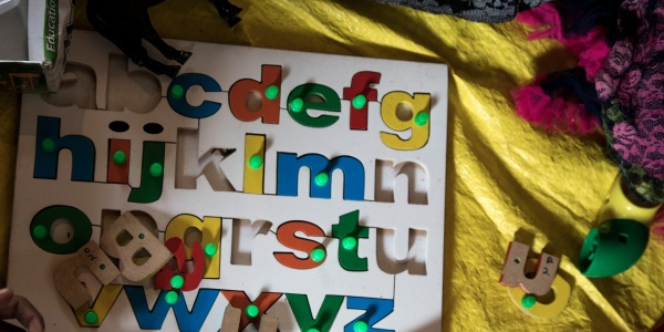 tabellone per bambini con lettere dell'alfabeto colorate estraibili poggiato su un lenzuolo giallo