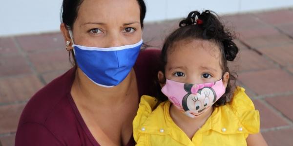 mamma con maglietta bordeaux tiene in braccio una bimba con maglietta gialla. Entrambe indossano una mascherina. Sono di carnagione chiara con capelli castani.