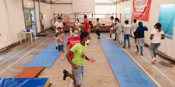 Bambini che corrono in cerchio in una palestra. A terra materassini azzurri