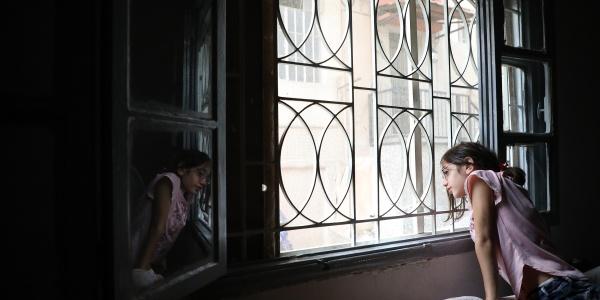 bambina in penombra si affaccia alla finestra appoggiando e mani su un mobile all interno