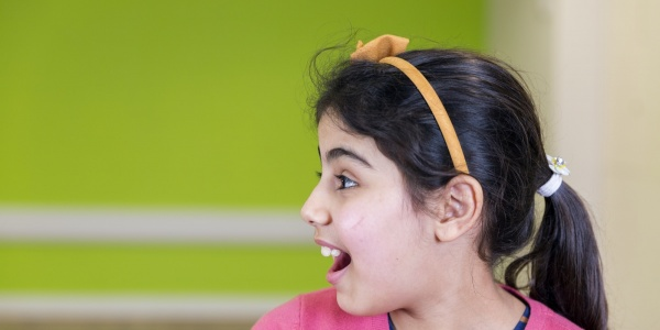 bambina di profilo con maglioncino rosa fa una smorfia di stupore