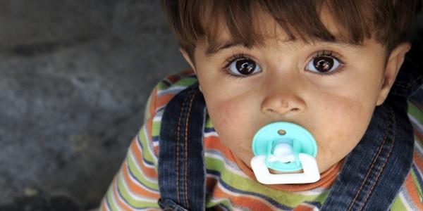 primo piano bambino bianco con capelli castani, occhi marroni, con un ciuccio azzurro in bocca guarda in camera.
