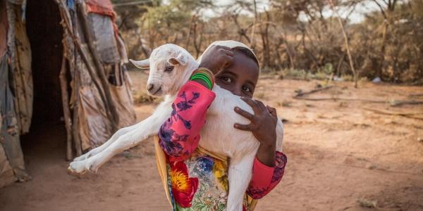 bimba somala con belo bianco e vestito lungo colorato con in braccio una capretta bianca fuori dalla sua abitazione in una zona semi desertica