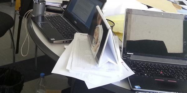 Due laptop appoggiati su un tavolo pieno di carte.