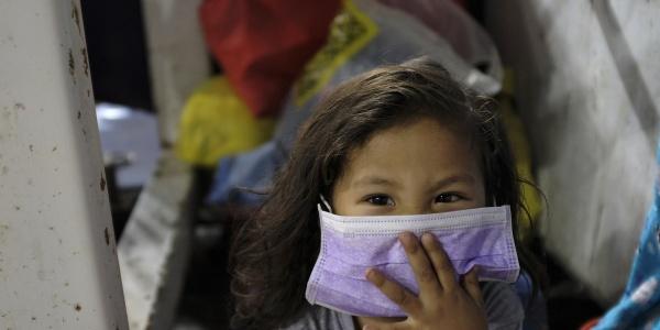 Bambina asiatica con mascherina viola sul viso