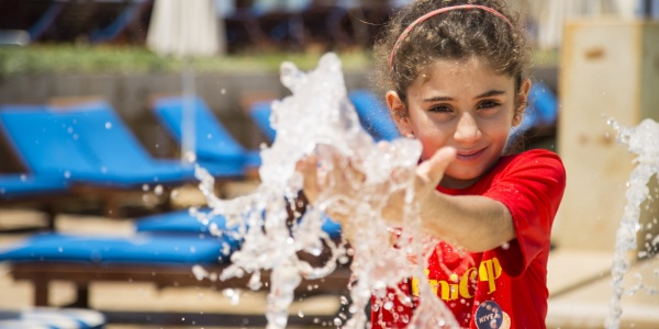 bambina bianca in primo piano con le mani tra lo spruzzo di una fontana