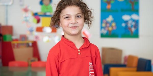 bambina sorridente con felpa rossa guarda in camera. Si trova in una scuola per l'infanzia.