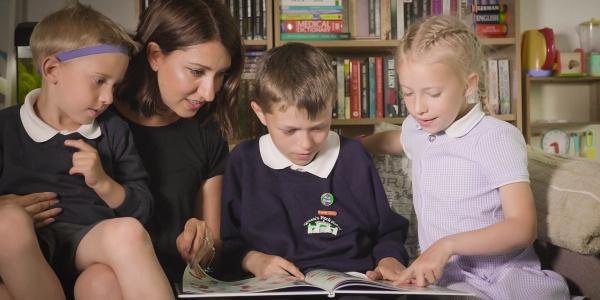 3 bambini con la mamma leggono libri in casa insieme