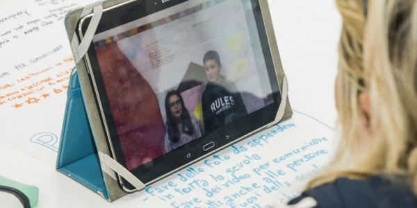 bambina bionda di spalle davanti a uno schermo di un tablet