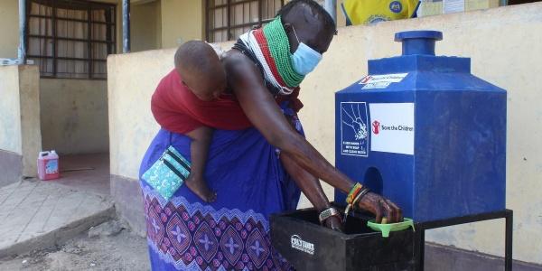 Mamma africana con bambino in fascia sulla schiena lava le mani con fontana mobile save the children.