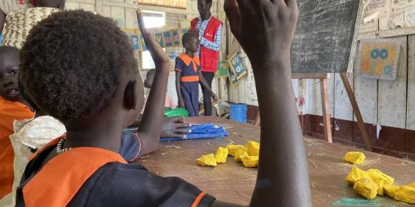 bambina ugandese di spalle con mano alzata durante lezione in classe