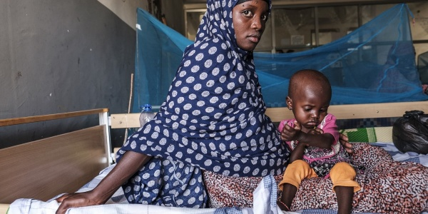 Mamma africana tiene in braccio bambino malnutrito entrambi sono seduto sul letto di una clinica
