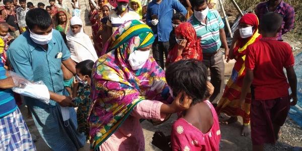 gruppo di persone di origine indiana durante una consegna di mascherine per proteggersi dal covid-19