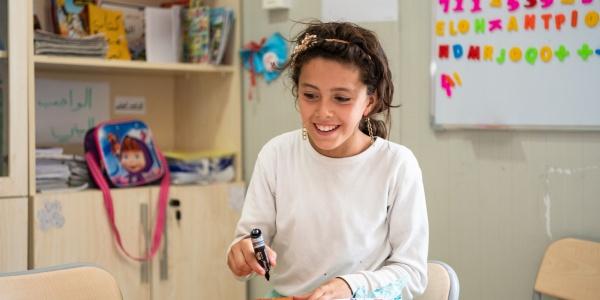 ragazza seduta a un tavolo fa lavori con carta, forbici e colori