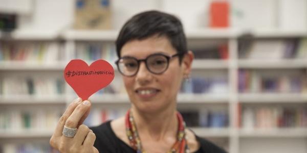 donna con capelli corti tiene in mane un cuore di carta con scritta #distantimavicini