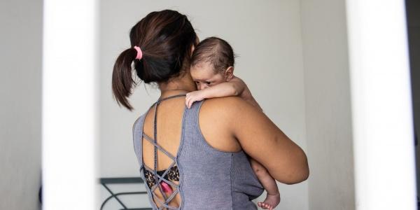 mamma con bambino neonato in braccio di spalle
