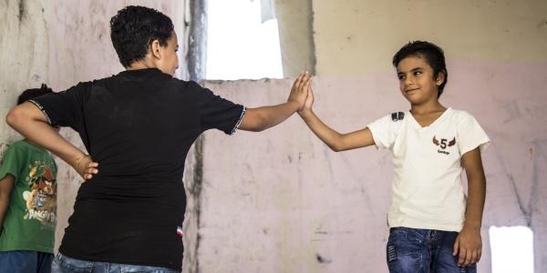 due ragazzi in piedi si danno il cinque con la mano