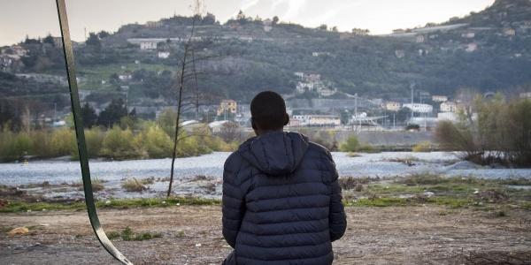 Minore straniero di spalle seduto a terra guarda panorama davanti a lui