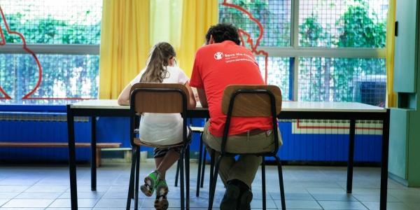 operatore save the children di spalle seduto a un tavolo con affianco una bambina seduta
