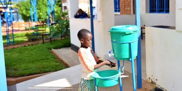 bambina del Rwanda lava le mani con rubinetto portatile
