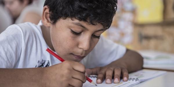 bambino seduto alla scrivania mentre fa i compiti