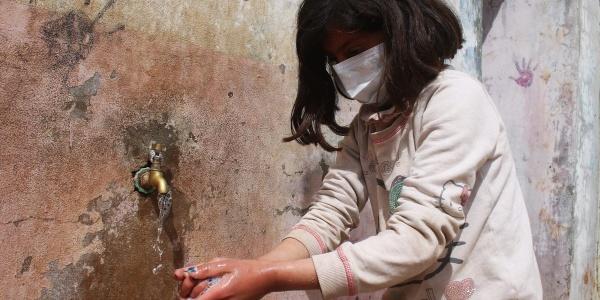 Bambina siriana con mascherina in volto si lava le mani a una fontana