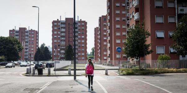 bambina di spalle cammina lungo una strada deserta a Milano tra i palazzi
