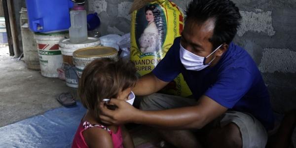 Un adulto sistema sul viso la mascherina su una bambina piccola seduta di fronte a lui.
