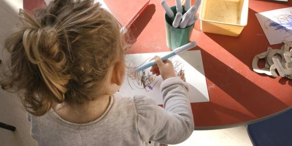 bambina di spalle alla scrivania che colora e disegna