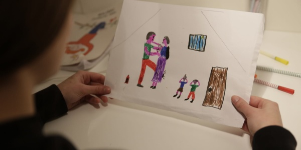 Bambina di spalle tiene in mano un disegno che rappresenta una scena di violenza domestica e assistita
