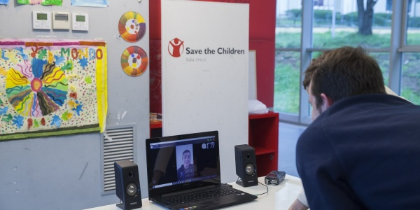 operatore di save the children italia davanti al pc in collegamento con un ragazzo
