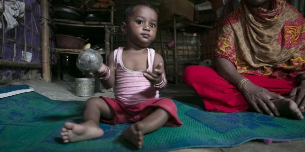 Bambino rohingya gioca seduto a terra
